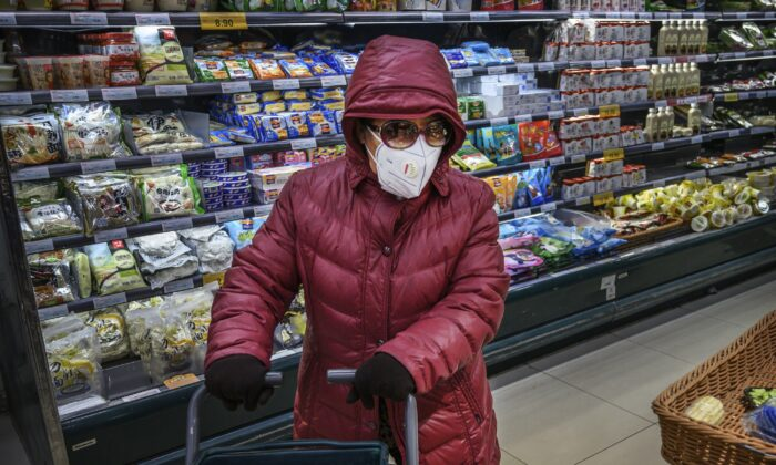 A Chinese woman wears a protective mask and sunglasses as she shops for groceries at a supermarket in Beijing on Jan. 28, 2020. (Kevin Frayer/Getty Images)