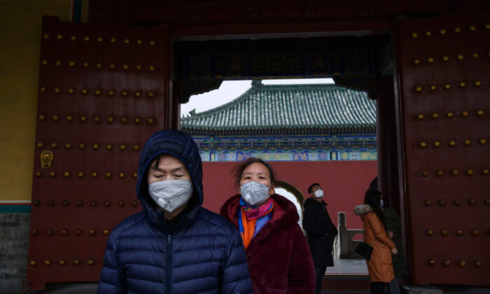 Chinese visitors wear protective masks as they tour the Temple of Heaven, which remained open during the Chinese New Year and Spring Festival holiday in Beijing, China, on Jan. 27, 2020. (Kevin Frayer/Getty Images)