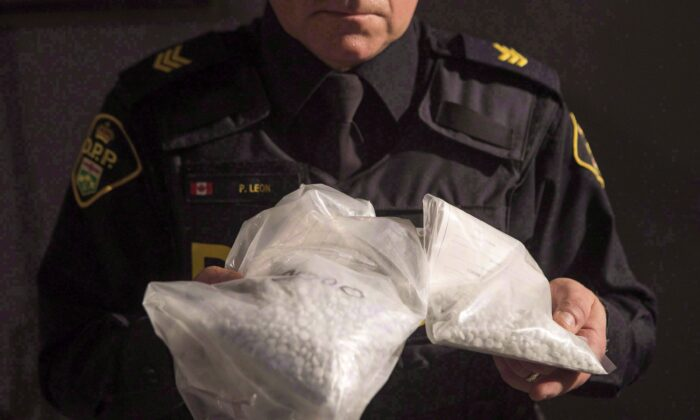 An Ontario Provincial Police officer displays bags of fentanyl during a news conference in Vaughan, Ont., Canada, on Feb. 23, 2017. (The Canadian Press/Chris Young)