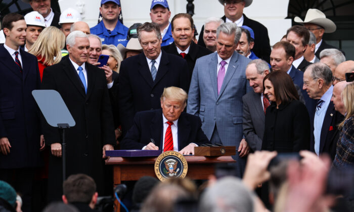 President Donald Trump signs the United States–Mexico–Canada Agreement, known as USMCA, during a ceremony on the South Lawn of the White House on Jan. 29, 2020. (Charlotte Cuthbertson/The Epoch Times)