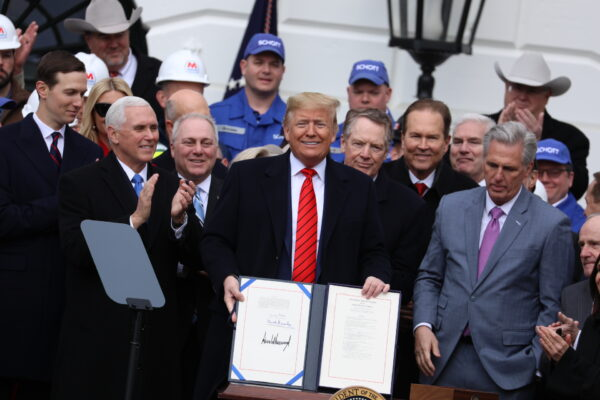 President Donald Trump holds up the signed USMCA agreement