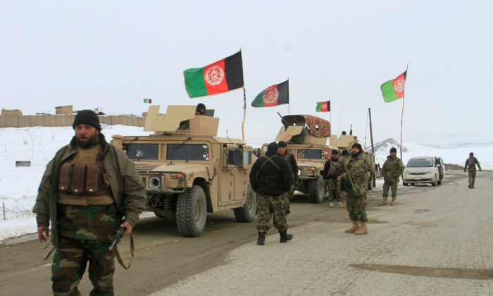 Afghan National Army forces go towards the site of an airplane crash in Deh Yak district of Ghazni province, Afghanistan on Jan. 27, 2020. (Mustafa Andaleb/Reuters-File)