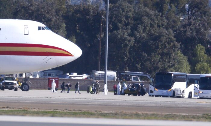 Passengers board buses after arriving on an airplane carrying U.S. citizens being evacuated from Wuhan, China, at March Air Reserve Base in Riverside, Calif., on Jan. 29, 2020. (Ringo H.W. Chiu/AP Photo)