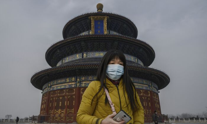 A Chinese visitor wears a protective mask as she tours the grounds of the Temple of Heaven in Beijing, on Jan. 27, 2020. (Kevin Frayer/Getty Images)