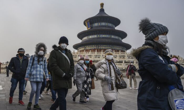 Visitors wear protective masks as they tour the grounds of the Temple of Heaven in Beijing on Jan. 27, 2020. (Kevin Frayer/Getty Images)