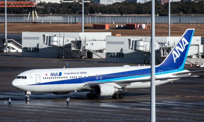 An airplane carrying Japanese citizens repatriated from Wuhan amidst the coronavirus outbreak lands at Haneda airport in Tokyo on Jan. 29, 2020. (Carl Court/Getty Images)