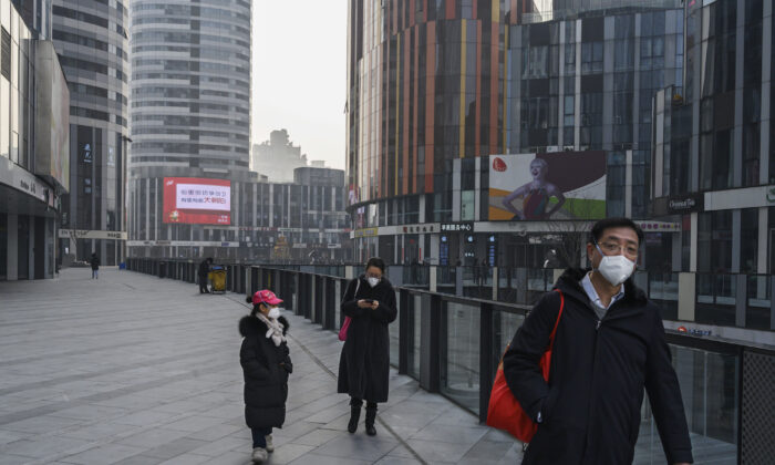 A Chinese family wears protective masks as they walk in an empty shopping area that would usually be busy during the Chinese New Year and Spring Festival holiday in Beijing, China on Jan. 28, 2020. (Kevin Frayer/Getty Images)