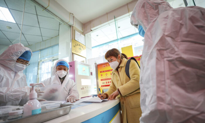 Medical workers in protective gear talk with a woman suspected of being ill with a coronavirus at a community health station in Wuhan in central China's Hubei Province, on Jan. 27, 2020. (Chinatopix via AP)
