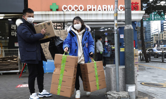 People leave after buying face masks at a pharmacy in Seoul, South Korea, on Jan. 29, 2020. (Ahn Young-joon/AP Photo)
