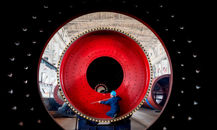 An employee measures a newly manufactured ball mill machine at a factory in Nantong, Jiangsu Province, China on June 28, 2019. (Reuters)