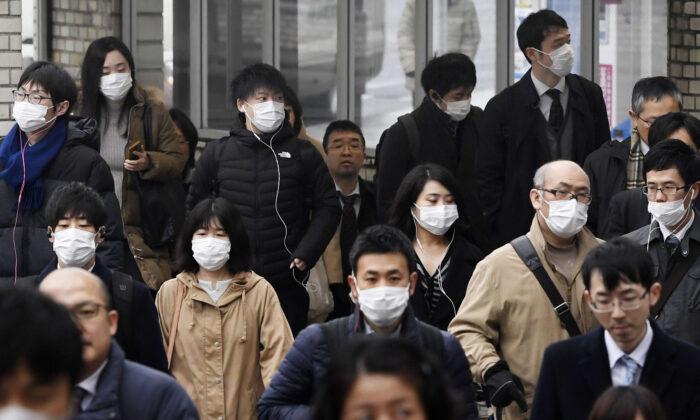 People wearing face masks walk on a street in Nara, western Japan, on Jan. 29, 2020. (Nobuki Ito/Kyodo News via AP)