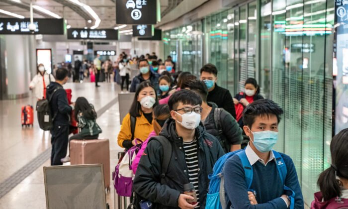 Travelers wearing protective masks wait in line for a ride after arriving at the Hong Kong High Speed Rail Station in Hong Kong, China, on January 29, 2020.  (Anthony Kwan/Getty Images)