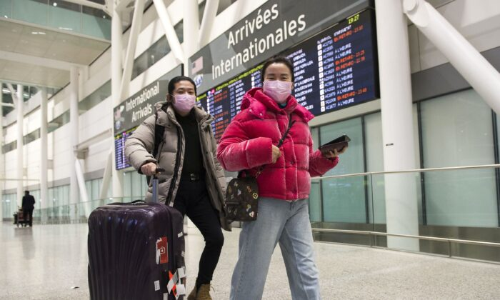 People wear masks as a precaution due to the coronavirus outbreak as they arrive at the International terminal at Toronto Pearson International Airport on Jan. 25, 2020. (The Canadian Press/Nathan Denette)