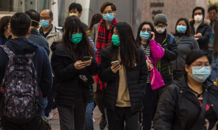 People wearing masks walk along a street in Hong Kong on Jan. 30, 2020. (Dale De La Rey/AFP via Getty Images)