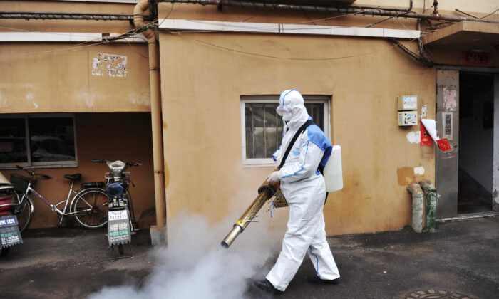 A worker wearing a protective suit sprays disinfectant in a neighborhood in Qingdao in eastern China's Shandong province on Jan. 28, 2020. (Chinatopix via AP)