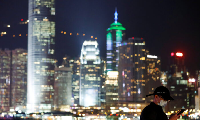 A man wears mask to prevent a new coronavirus outbreak as he uses his mobile, with skyline in the background of Hong Kong, China, on Jan. 29, 2020. (Tyrone Siu/Reuters)