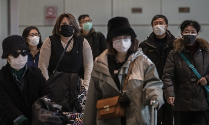 Passengers wear protective masks as they arrive at Beijing Capital Airport in Beijing, China, on Jan. 30, 2020. (Kevin Frayer/Getty Images)