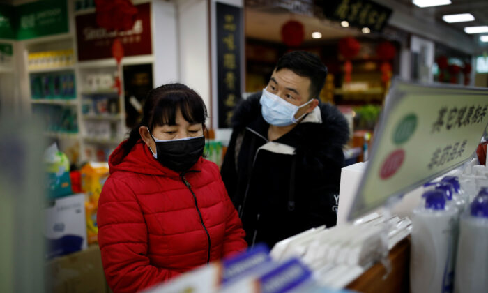 People wearing face masks look for products at a pharmacy as the country is hit by an outbreak of the new coronavirus, in Beijing, China Jan. 30, 2020. (Reuters/Carlos Garcia Rawlins)