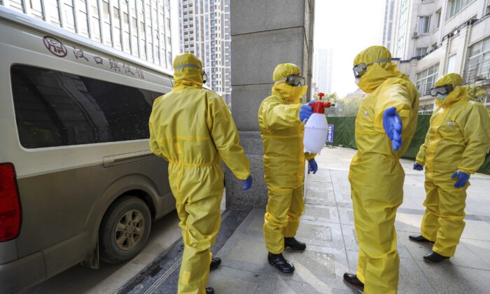 Funeral workers disinfect themselves after handling a virus victim in Wuhan in central China's Hubei Province on Jan. 30, 2020. (Chinatopix via AP)