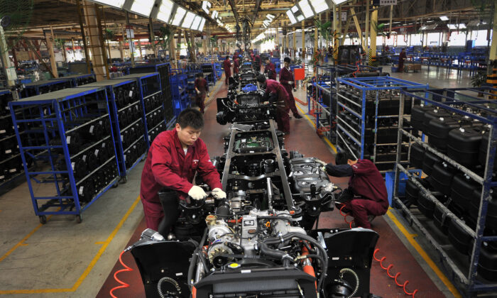 Workers install the chassis along a production line at a truck factory of Anhui Jianghuai Automobile Co. Ltd. (JAC Motors) in Hefei, Anhui Province, China on May 5, 2014. (Reuters)
