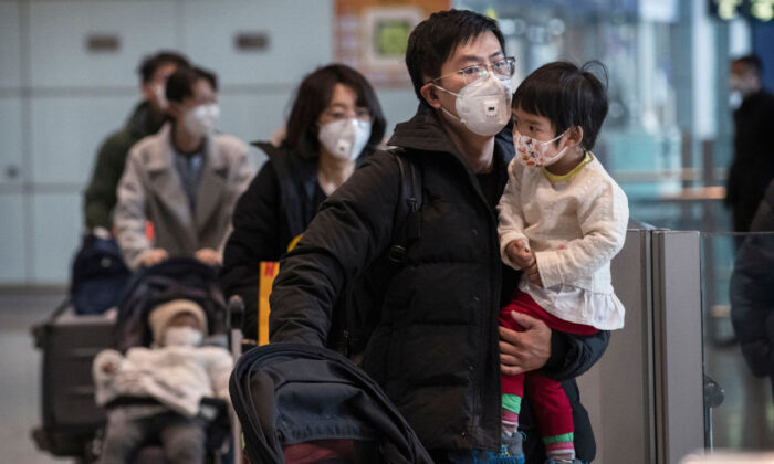 Passengers wear protective masks as they walk their luggage in the arrivals area at Beijing Capital Airport in Beijing, China, on Jan. 30, 2020. (Kevin Frayer/Getty Images)