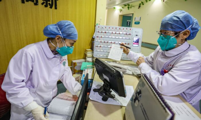 Medical staff members wearing face masks talking at a hospital in Wuhan, China on Jan. 30, 2020. (STR/AFP via Getty Images)