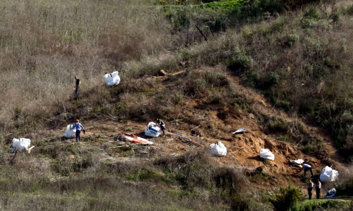 Personnel collect debris while working with investigators at the helicopter crash site of NBA star Kobe Bryant in Calabasas, California on Jan. 28, 2020. (Patrick T. Fallon/Reuters)
