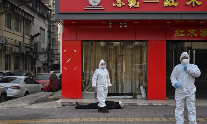 Chinese officials in protective suits checking on an elderly man wearing a facemask who collapsed and died on a street near a hospital in Wuhan, China, on Jan. 30, 2020. (Hector Retamal/AFP via Getty Images)