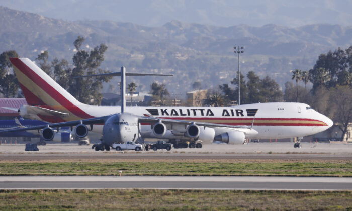 An airplane carrying U.S. citizens being evacuated from Wuhan, China, lands at March Air Reserve Base in Riverside, Calif., on Jan. 29, 2020. (Ringo H.W. Chiu/AP Photo)