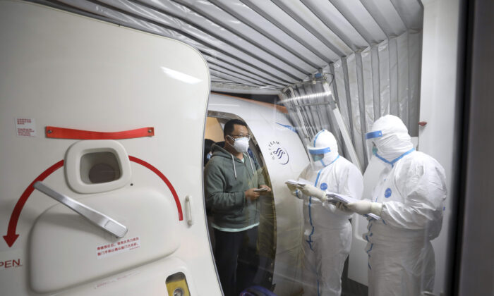 Quarantine workers in protective suits check identity documents as tourists from the Wuhan area walk off of a chartered plane taking them home from Bangkok at Wuhan Tianhe International Airport in Wuhan in central China's Hubei Province on Jan. 31, 2020. (Chinatopix via AP)