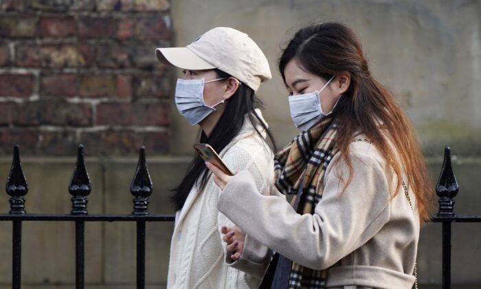 Two women wearing face masks walk through the city center near to the Royal Victoria Infirmary where two patients who have tested positive for the Wuhan coronavirus are being treated by specialist medical workers in Newcastle, England, on Jan. 31, 2020. (Ian Forsyth/Getty Images)
