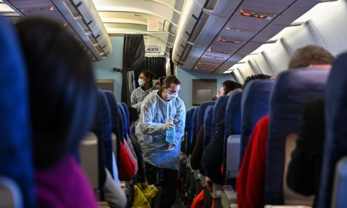 A crew member of an evacuation flight of French citizens from Wuhan gives passengers disinfectant during the flight to France on Feb. 1, 2020. (Hector Retamal/AFP via Getty Images)
