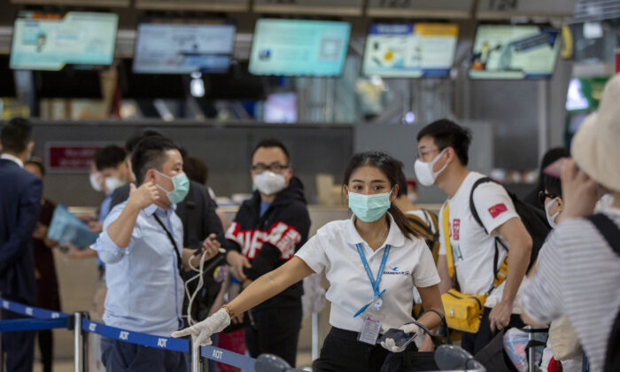 An airline staffer who assist a charter flight, guides Chinese tourists from Wuhan, who stand in a line to get a seat to return to Wuhan at Suvarnabhumi airport, Bangkok, Thailand, on Jan. 31, 2020. A group of Chinese tourists who have been trapped in Thailand since Wuhan was locked down due to an outbreak of new virus returned to China on Friday. (Gemunu Amarasinghe/AP)