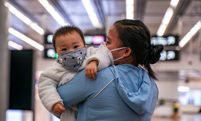 A woman carries a baby wearing a protective mask as they exit the arrival hall at Hong Kong High Speed Rail Station in Hong Kong, on Jan. 29, 2020. (Anthony Kwan/Getty Images)