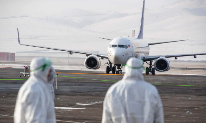 Staff members, wearing protective suits, watch as a plane carrying 32 Mongolian citizens for their evacuation from the Chinese city of Wuhan arrives in Ulaanbaatar, the capital of Mongolia on Feb. 1, 2020. (Byambasuren Enbyamba-OChir/AFP via Getty Images)
