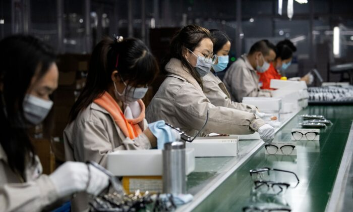 Workers wear protective masks while polishing eyeglass frames at the Azure Eyeglasses Co. in Wenzhou, China, on Feb. 28, 2020.  (Noel Celis/AFP via Getty Images)