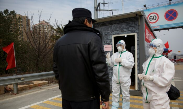Hospital staff in protective clothing talk to a police officer at a checkpoint to the Hubei province exclusion zone at the Jiujiang Yangtze River Bridge in Jiujiang, Jiangxi province, China, as the country is hit by an outbreak of a new coronavirus on Feb. 1, 2020. (Thomas Peter/Reuters)