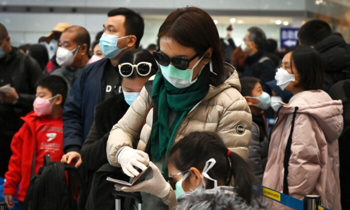 A woman wears a protective face mask and gloves while waiting to go through immigration at Beijing airport on Feb. 1, 2020. (Greg Baker/AFP via Getty Images)