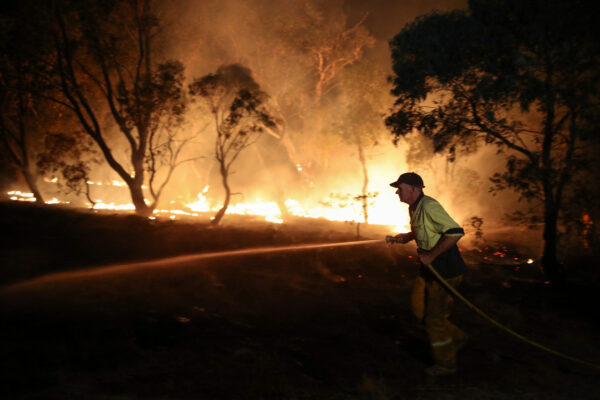 A firefighter works to extinguish flames after a bushfire burnt through the area in Bredbo