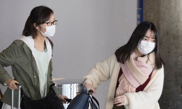 Passengers wear face masks to protect against the spread of the Coronavirus as they arrive on a flight from Asia, at Los Angeles International Airport, Calif., on Feb. 1, 2020. (Mark Ralston/AFP via Getty Images)