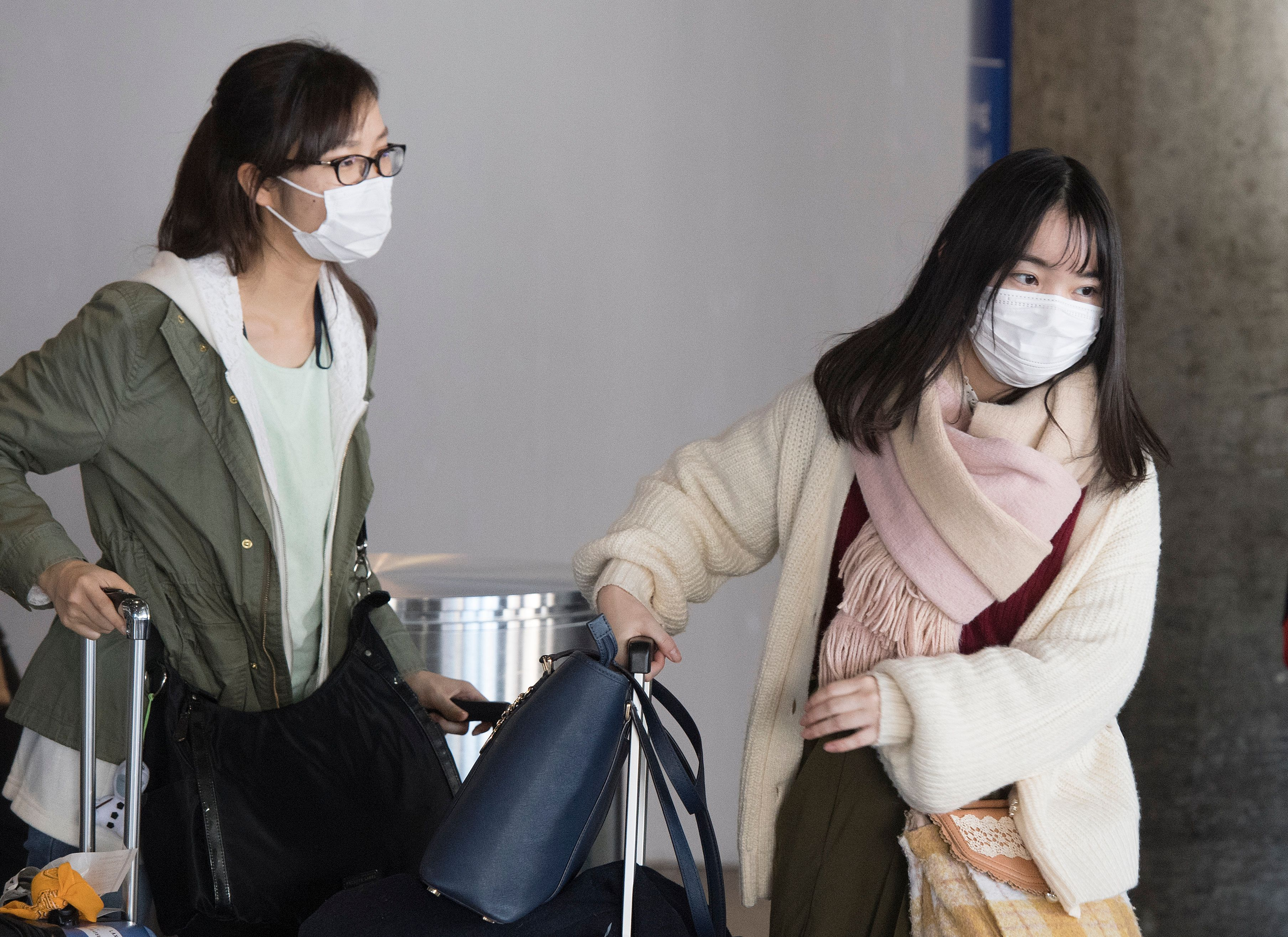 Passengers wear face masks to protect against the spread of the Coronavirus