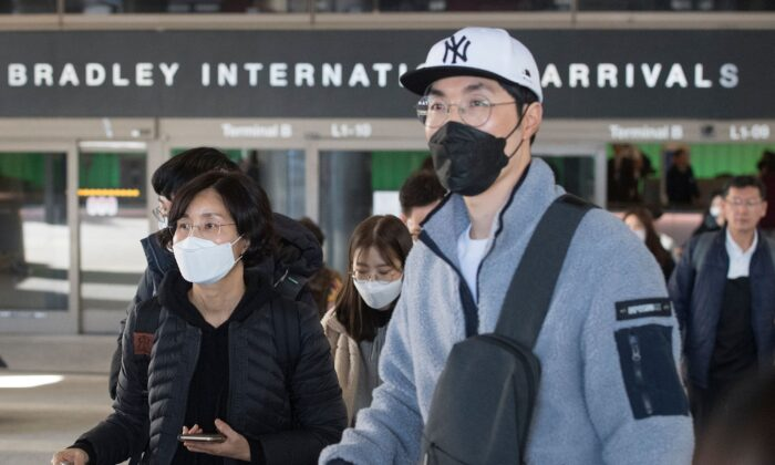 Passengers wear protective masks to protect against the spread of the Coronavirus as they arrive on a flight from Asia at the Los Angeles International Airport, Calif., on Jan. 29, 2020. (Mark Ralston/AFP via Getty Images)