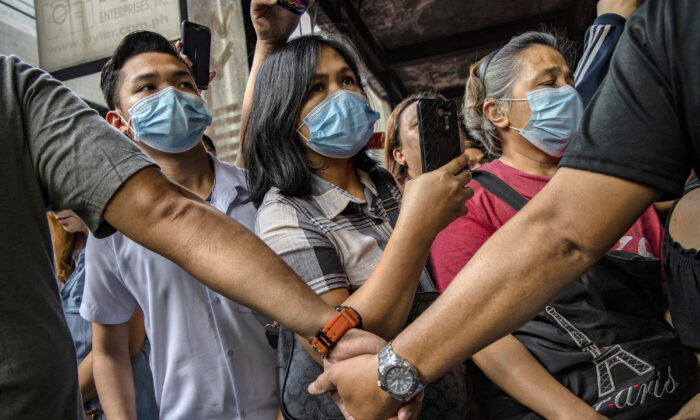 Police officers stand guard as Filipinos hoping to buy face masks crowd outside a medical supply shop that was raided by police for allegedly hoarding and overpricing the masks, as public fear over China's Wuhan Coronavirus grows in Manila, Philippines, on Jan. 31, 2020. (Ezra Acayan/Getty Images)