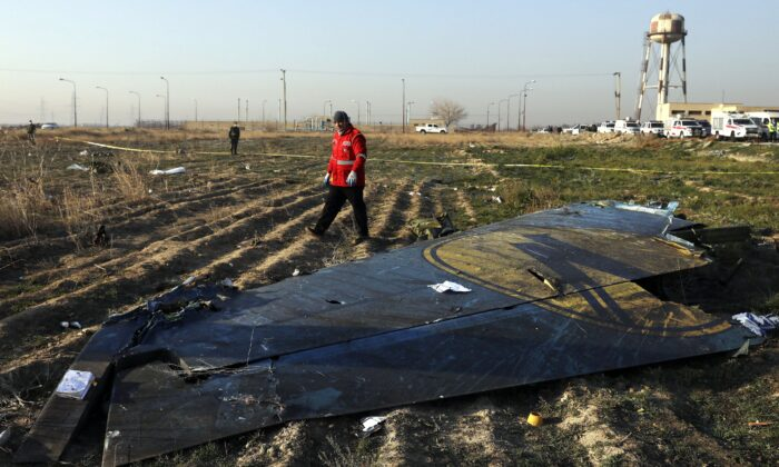 A rescue worker searches the scene on Jan. 8, 2020, where a Ukrainian plane crashed southwest of Tehran, Iran, killing all 176 people on board. (AP Photo/Ebrahim Noroozi)