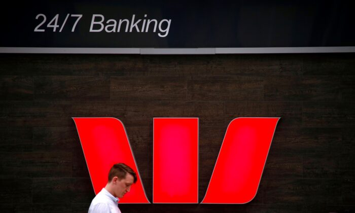 A pedestrian looks at his phone as he walks past a logo for Australia's Westpac Banking Corp located outside a branch in central Sydney, Australia, on Nov. 5, 2018. (David Gray/Reuters/File Photo)