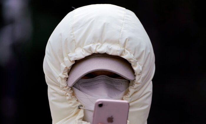 A woman wearing a mask checks her mobile phone in Shanghai, China on Jan. 29, 2020. (Aly Song/Reuters)