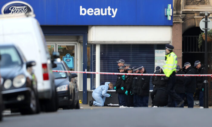 Police officers and forensic officer are seen near the site where a man was shot by armed officers in Streatham, south London, Britain, on Feb. 3, 2020. (Antonio Bronic/Reuters)