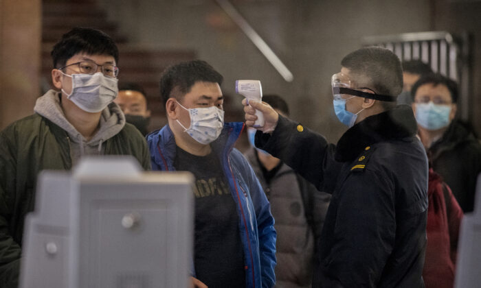 A Chinese passenger who just arrived on the last bullet train from Wuhan to Beijing is checked for a fever by a health worker at a Beijing railway station in Beijing on Jan. 23, 2020. (Kevin Frayer/Getty Images)