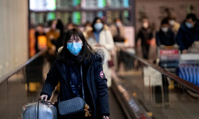 A passenger wearing a protective facemask looks on as she arrives at the Beijing Capital International Airport in Beijing on Feb. 2, 2020. (Noel Celis/AFP via Getty Images)