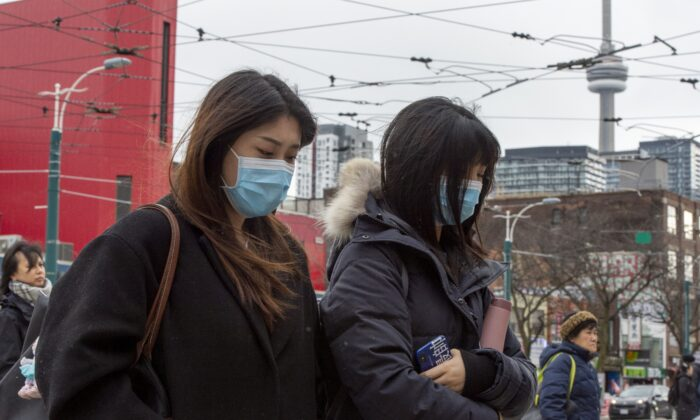 Pedestrians wear protective masks as they walk in Toronto on Jan. 27, 2020. Parents and other primary caregivers will accompany their Canadian children back to Canada after leaving Wuhan, the epicentre of an outbreak of the novel coronavirus, even if they are not citizens themselves. (The Canadian Press/Frank Gunn)